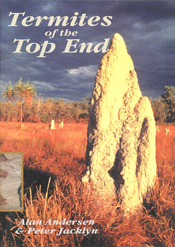 The cover image featuring a large termite tower, in red grass, with dark g